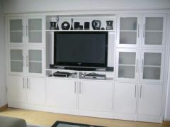 The built-in cabinet shown here presents a large television encompassed by a combination of solid and frosted inset glass doors. Nicely complemented by contemporary bar pulls, it holds a lot, fits right and looks good.